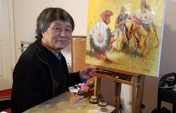 Professor Yan Sun sitting in front of one of his paitings of Native Americans holding his brush and pallette